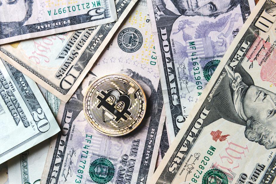 bitcoin-coin-on-bills-of-cash-money_925x